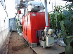 ハウスに設置された加温用ボイラー 重油用の燃焼機をペレット用に置き換えることができる